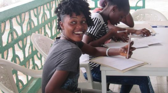 A laughing teenager at Mineke Foundation looks away from the camera