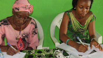Two ladies writing at a table at Mineke Foundation