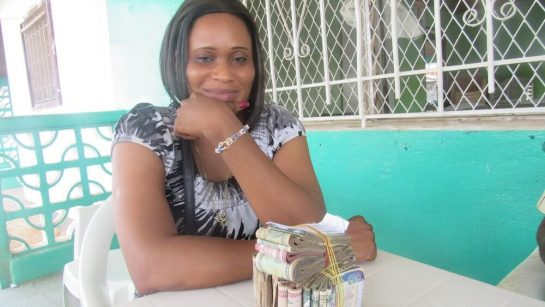 A woman sits at a table with a stack of money in front of her at Mineke Foundation
