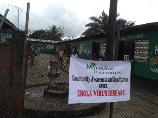 A banner informs community members about Mineke Foundation's Ebola awareness meetings